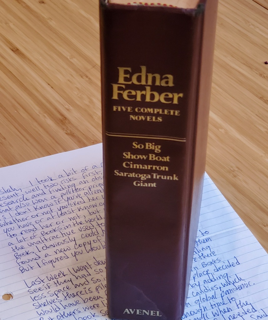 Photograph of a burgundy compilation of five novels by Edna Ferber, on top of a handwritten letter, sitting on a multi-toned, light colored surface.
