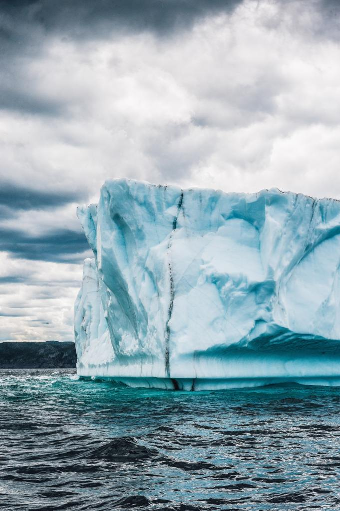 A large iceberg in the ocean under a cloudy sky.